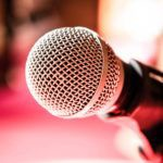 Close up of microphone in karaoke room or conference room.  red background (microphone, karaoke, music )